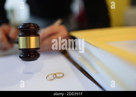 Judge holding wooden gavel near two wedding rings close-up