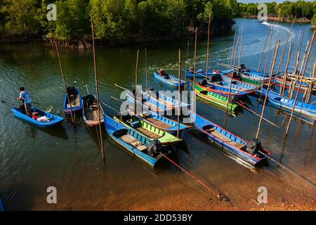 Colourful traditional Asian wooden fishing boats at a local port in mangrove forest. Ranong, Thailand. High angle view.