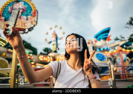 Beautiful young woman taking selfie through smart phone while gesturing peace sign at amusement park during summer