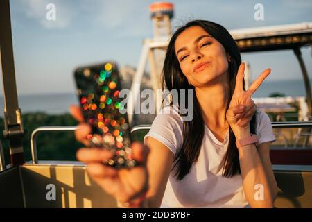 Beautiful young woman taking selfie through mobile phone while puckering and gesturing peace sign on Ferris wheel