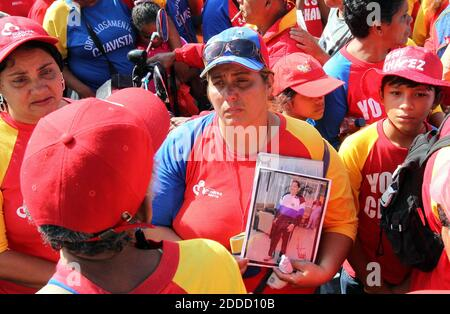 NO FILM, NO VIDEO, NO TV, NO DOCUMENTARY - A supporter of Venezuelan President Hugo Chavez holds his picture as she waits for his funeral procession to pass in Caracas, Venezuela, on Wednesday, March 6, 2013. Escorted by his family, friends and governement members, the procession makes its way to the Military Academy for a final tribute that will last through Friday. Photo by Pedro Portal/El Nuevo Herald/MCT/ABACAPRESS.COM