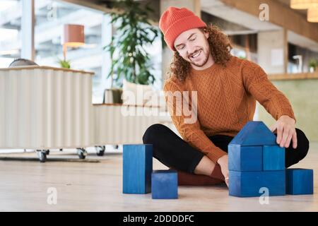 Hipster man playing with toy block while sitting on floor in living room at home - Stock Photo