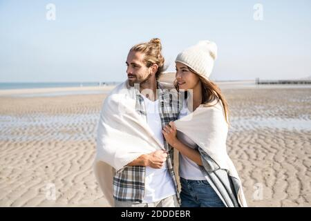 Thoughtful young couple covered in blanket looking away while standing at beach on sunny day Stock Photo