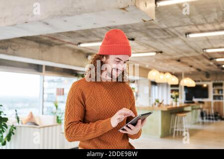Smiling hipster man using digital tablet while standing in living room at home - Stock Photo
