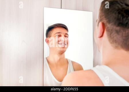 Happy Young Man looking to Reflection in the Mirror at the Home