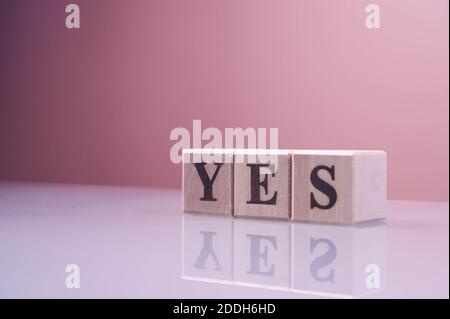 Text YES on wood cube blocks. The letters YES written on the cubes in black letters isolated on a glass surface. YES text for your desing.