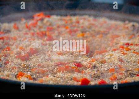 Process of cooking paella shrimp, mussel, rice, tomato in huge pan - close up - Stock Photo