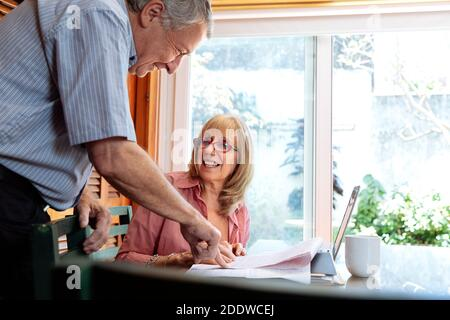 A senior woman and man smiling and talking about business. The woman is an a table with a laptop in front of her. Clear light image.