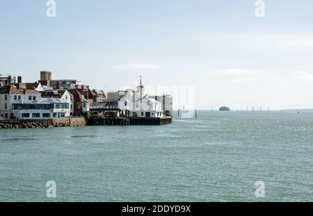 Portsmouth, UK - September 8, 2020: View across Portsmouth Harbour towards the historic Portsmouth Point area of pubs and fortifications seen on a sun - Stock Photo