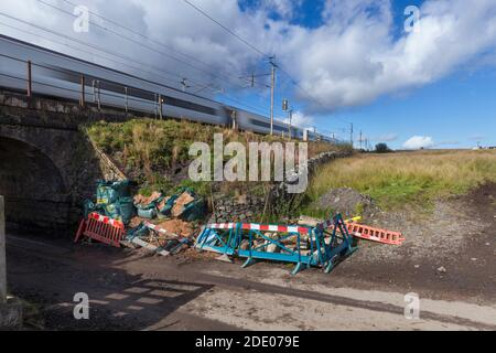 Temporary shoring up of a damaged retaining wall and embankment on the Network rail west coast mainline in Cumbria - Stock Photo