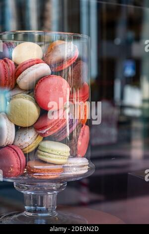 Macarons in a glass jar. French colorful delicate sweets assortment, vertical. Candy store window display