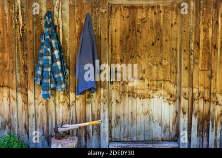 Two wooden axes stuck in the wood chopping trunk. In the background, a wooden wall of the house and two working clothes hanging on a hook.