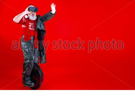 Happy modern Santa Claus riding on fast black monowheel wearing virtual reality 3d glasses and biker clothes. Winter and new tears eve holiday celebra
