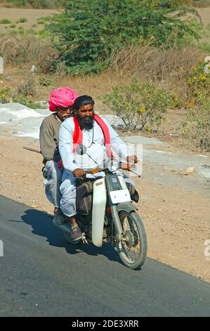 Riding on a scooter in rural Rajasthan, India Stock Photo