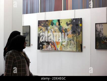 Baghdad. 29th Nov, 2020. People watch a painting during the al-Wasiti festival in Baghdad, Iraq, Nov. 28, 2020. The Iraqi Ministry of Culture holds the 13th al-Wasiti festival in Baghdad, in which many artworks reflect the COVID-19 pandemic. Credit: Xinhua/Alamy Live News