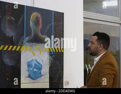Baghdad. 29th Nov, 2020. A man looks at a painting about COVID-19 during the al-Wasiti festival in Baghdad, Iraq, Nov. 28, 2020. The Iraqi Ministry of Culture holds the 13th al-Wasiti festival in Baghdad, in which many artworks reflect the COVID-19 pandemic. Credit: Xinhua/Alamy Live News