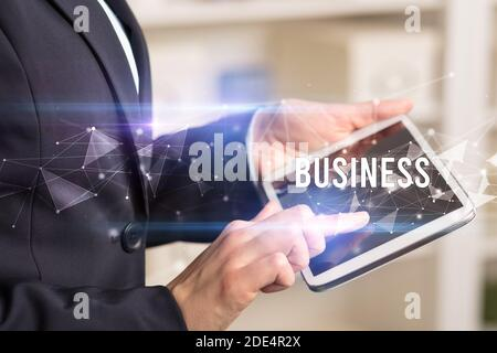 Close up hands using tablet with BUSINESS inscription, modern business technology concept
