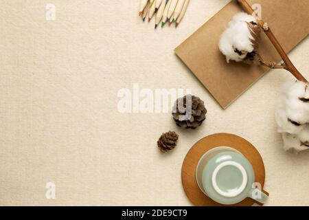 Winter concept. Work and study place. Notebook, mug cup, colored pencils, cotton plant on beige fabric background. flat lay, top view, copy space - Stock Photo