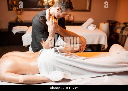 Professional therapist doing a deep massage to a male client at Spa salon. working on the lower body, stretching leg