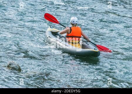Young woman floats by inflatable boat on the mountain river. - Stock Photo