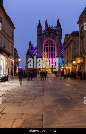 Bath Abbey lit with colourful illuminations and a bright tall Christmas tree. Part of the 2020 Christmas Light Trail in Bath City Centre, England, UK - Stock Photo