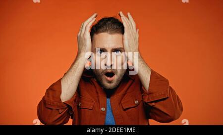 shocked young man looking at camera on orange