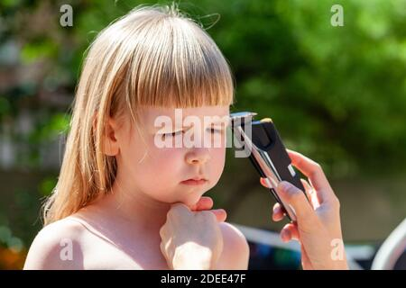 Parent, mother cutting her daughters hair using an electric hair trimmer, electrical hair clipper home use Amateur simple children haircut
