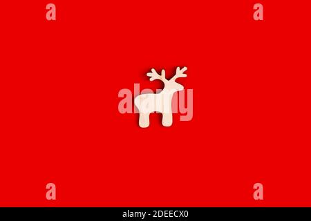Deer figurine, flat, natural, unpainted wooden shape on a red background. - Stock Photo