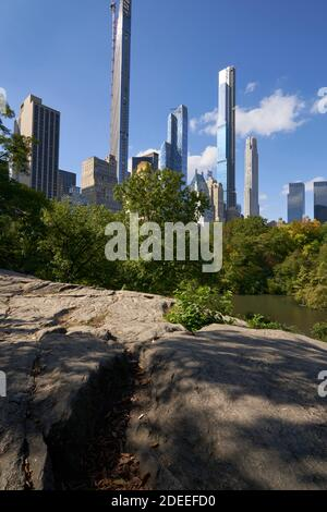 Skinny tall buildings towering over Central Park in New York City