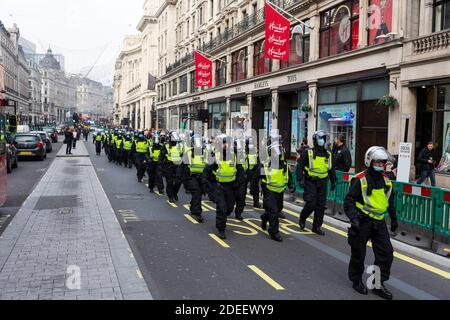 Anti-lockdown protest, London, 28 November 2020. Police officers in riot gear march down Regent Street. Stock Photo