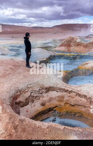 Man standing in front of some mud pits with volcanic activity in the Andean Highlands, Bolivia.