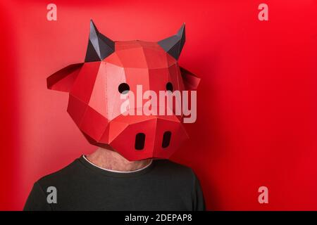 Young man in red 3d mask of bull cow on the head on an isolated background. Close up portrait person. Blank for banner, template, place for advertisin - Stock Photo