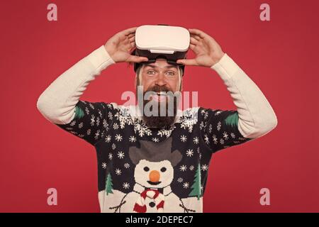 man winter sweater play game. indoor vs outdoor activity. Virtual reality. man wearing virtual reality goggles. xmas party. happy bearded hipster in vr glasses. interacting with a virtual environment