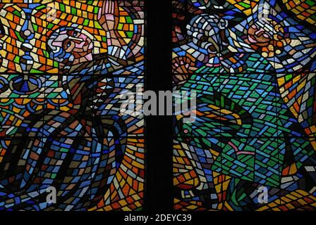 Man and woman in 1700s or early 1800s costume kneel at bedside of sick child in detail of kaleidoscopic mosaic stained glass in the Cathedral of St Vitus by Czech Modernist and Impressionist painter, graphic artist and stage designer František Kysela (1881-1941).  Kysela was a versatile and prolific artist who also designed textiles, carpets, tapestries, stage costumes, posters, bookplates, diplomas, banknotes and postage stamps.  His book illustrations were inspired by Renaissance prints and medieval woodcuts.  His stained glass for Prague Cathedral was created between 1921 and 1936. - Stock Photo