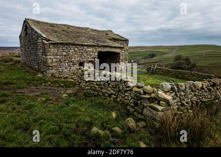Crooked old stone barn with wooden stile and the B6265 in the background near Hebden and Burnsall, Yorkshire Dales National Park, North Yorkshire, Eng