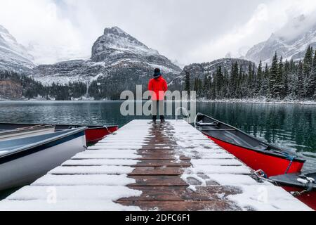 Man traveler standing on wooden pier with red canoe and snowing in Lake O'hara at Yoho national park, Canada - Stock Photo