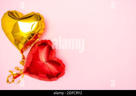 Red and golden hearts foil balloons upper view on pink Valentines Day background. Copyspace - Stock Photo