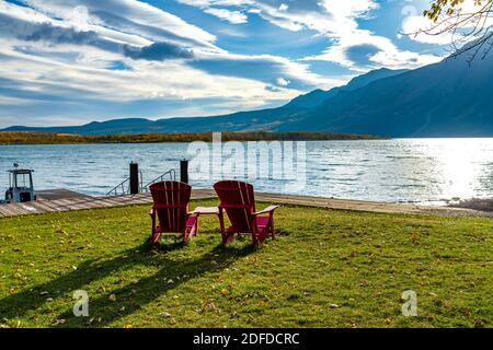 Red chair look over Middle Waterton Lake boat launch in autumn foliage season morning. Sunlight passing blue sky and clouds on mountains.Waterton Lake