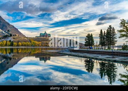 Waterton Lakes National Park lakeshore in autumn foliage season morning. Blue sky, colourful clouds reflect on lake surface like a mirror in sunrise.
