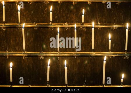 Horizontal shot of three rows of burning candles in Okunoin temple complex where Kobo Daishi, Wakayama, Koyasan, Japan
