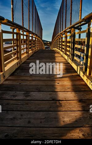 Perspective of a bridge with focus on the wooden floor and metal fence at sunset time - Stock Photo