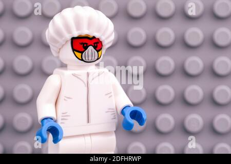 Tambov, Russian Federation - April 30, 2020 Lego Scientist minifigure in protective suit against gray baseplate. - Stock Photo