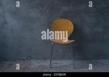 in front of a freshly plastered grey house wall stands a yellow chair - Stock Photo