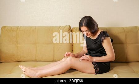 Barefoot brunette in black nightie applies white cream on thigh bruises sitting on brown sofa at home copyspace