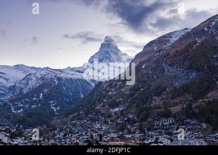 The Swiss village of Zermatt in Valais in autumn at dusk, with the Matterhorn and the Alpine mountain range in the background.