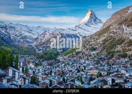 The Swiss village of Zermatt in Valais in autumn at sunrise, with the Matterhorn and the Alpine mountain range in the background.