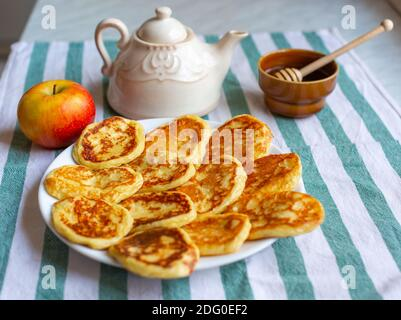 Tasty homemade pancakes laid out on plate near an apple, teapot and bowl of honey . Selective focus on pancakes