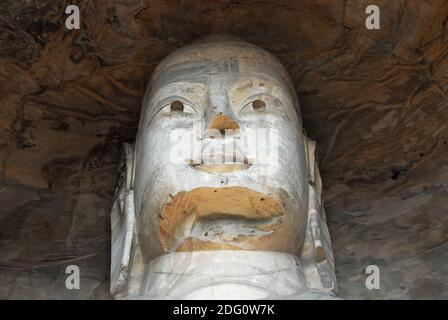Yungang Grottoes near Datong in Shanxi Province, China. Large ancient statue of Buddha in a cave at Yungang showing detail of the head. Stock Photo