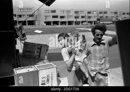 Moving house, family move into new home on a new estate1970s .Father and oldest daughter who is carrying her baby sister. Packing cases, old tea chests coming off the removal van. 1977  Milton Keynes Buckinghamshire UK HOMER SYKES - Stock Photo