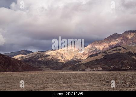 A view of Artist's Pallete in Death Valley National Park on a sunny day with dramatic clouds.